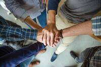 Top view of people joining hands together as a symbol of partnership