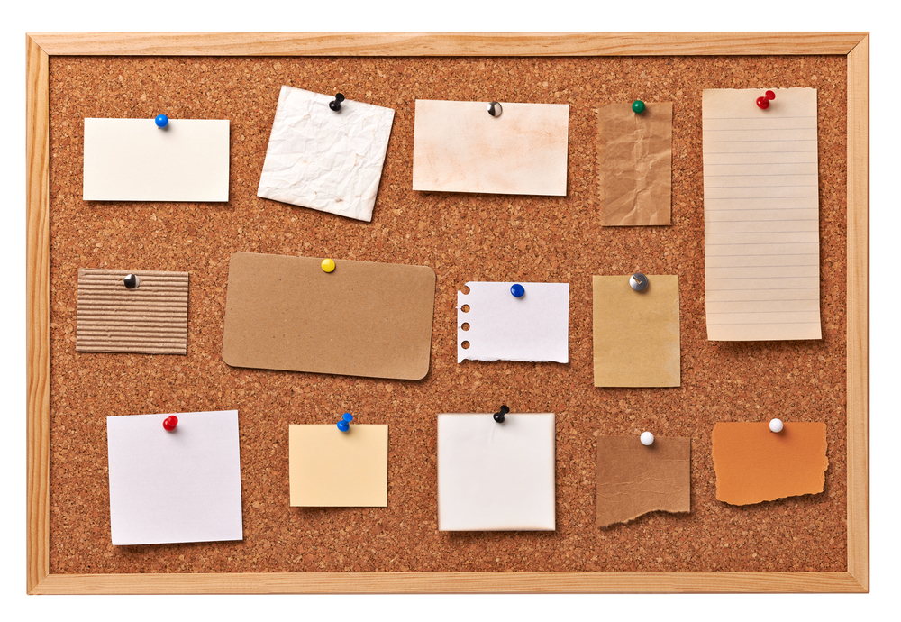 close up of note papers on a cork board